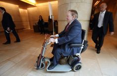Billionaire Sheldon Adelson, chairman and chief executive officer of Las Vegas Sands Corp., rides a mobility scooter as he leaves a news conference in Tokyo on Feb. 24, 2014.