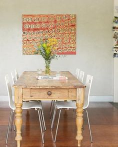Rustic wooden table with modern white chairs. Contrast, character and warmth. Perfect for the dining room.