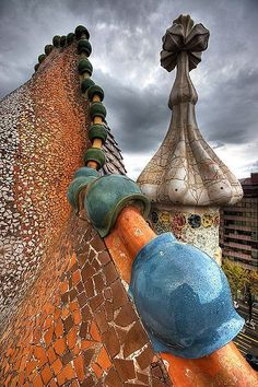 Para cubrir los depósitos de agua, Gaudí diseñó un tejado muy inclinado que parece una especie de gigantesco pez, realizado también con piezas de cerámica. La torre está rematada por una cruz con formas vegetales. Las texturas de los diferentes elementos son de una extraordinaria variedad y belleza.