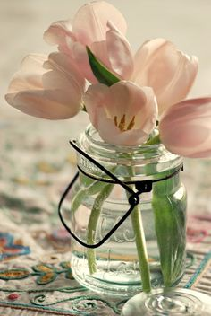 Blue mason jars with peach tulips will hanging from the aisle chairs at the ceremony site.