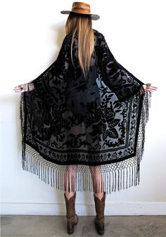 """Stevie Nicks inspired...total bohemian babe goodness with a vintage vibe.  Black on black velvet burnout with fishnet fringe dripping down the front, all along bottom, and sleeves!So many ways to wear dressed up or down, a truly timeless and effortless piece!Shown on a sz 2 model Will fit a wide range of sizes. Recommended for up to a sz 12. Measurements taken while garment is laid flat and open: Bust up to 43"""" Shoulder 20.5"""" Length including fringe 50""""..."""