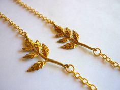 Pulseira de corrente dourada, com pingente de folha.