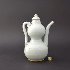 A Yuan Qingbai Porcelain double gourd shaped ewer and cover. Yuan Dynasty, probably Jingdezhen Kilns, Jiangxi Province, c.1300-1340. The handle in the form of an elongated dragon. The hand modelled dragon is crisply rendered and the whole ewer has a good bright clear glaze of a pale green blue.