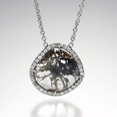 """An 18k white gold necklace with a 1.32ct center gray diamond slice and 38 pave diamonds totaling .20cttw, Chain measures 18"""". Pendant measures approximately 15mm x 15mm."""