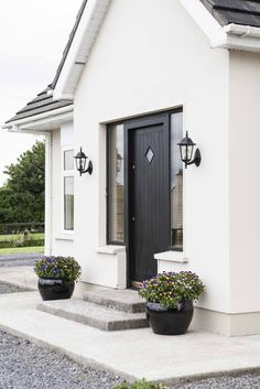 A sleek black front door never fails to impress. Raise the style stakes with wall-mounted lighting and a pair of planters Dark Front Door, Front Door Porch, House Front Door, Exterior Colors, Exterior Paint, Exterior Design, Interior And Exterior, Bungalow Exterior, White Houses