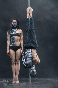 Posing of pole dance couple in dark studio by bezikus