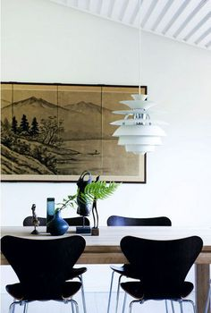 A PH Snowball pendant from Louis Poulsen hangs above a dark wood table and black Arne Jacobsen Series 7 chairs in this original Jørn Utzon-designed home in Denmark.