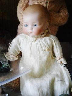 Collectible dolls including Putnam Bisque baby doll, Effanbee compo Snuggles with glass eyes, vintage Nurse and Girl Scout dolls, doll bed and quilt, plastic 1940's dolls in costume, cloth Deco pajama doll, and others.