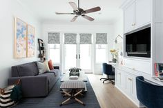 Side-by-side art hangs over a gray family room sofa accented with gray and orange pillows and placed on a blue rug facing a gray oak coffee table placed beside a black stripe x-stool. Office Built Ins, Built In Desk, Grey Family Rooms, Blue Home Offices, Deeper Shade Of Blue, Ceiling Trim, Entry Wall, Grey Desk, White Walls