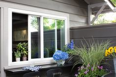 """An outdoor countertop and window pass-through make entertaining and meal preparation a breeze. """"It's a beautiful space when its open and you're grilling,"""" says Brian. """"When you have friends over you can easily pass drinks out the window or if you're eating inside someone can grill and pass it over to you."""""""