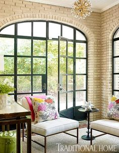 Steel doors and brick walls are balanced by delicate furniture and floral pillows in the sunroom. - Traditional Home ® / Photo: Lisa Mowry / Design: Katie Rosenfeld