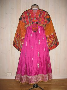 Woman's dress . The Kakarh are mountain people, clinging to ancient beliefs. Often they remove the skirt of a draws before selling it, considering it too intimate for others to own. Pieced from several older embroideries, the dress top combines areas of dense stichery with others of fabric, such as satin and gold brocade. Patterns are geometric or stylized floral: black pompoms punctuate the bodice front.