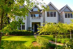 Gray shingle siding pairs with cream accents on the exterior of this colonial home. A beautifully landscaped front yard makes a grand first impression.