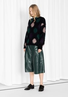 Fuzzy merino wool is knitted into playful circle-patterns, building up a comfy warmth-bringing sweater.
