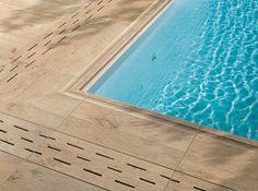 The LASTRA porcelain tile collection from Atlas Concorde includes features like trim pieces with built-in drains designed specifically for poolside decking.