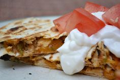 Grilled chicken quesadillas. A quick, easy, cheap appetizer or meal for Cinco De Mayo.  The inside is filled with melted cheese, grilled chicken and veggies and a variety of mexican spices layered between two crips tortillas.  Topped with sour cream and a freshly sliced tomato - absolutely delicious!