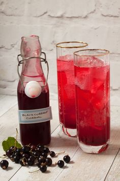Bottle of homemade blackcurrant cordial by recipes made easy with two glasses of cordial to the side.