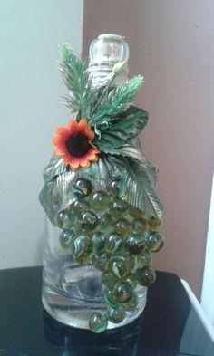 Garrafa decorada com folhas e bolinhas de gude.