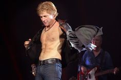 """The Intimate Stories Behind the Photos of the 'Bon Jovi: Work' Book - n a rare moment and to the delight of the audience, Jon Bon Jovi takes off his shirt on stage in Fresno, Calif., on Oct. 8, 2013. """"He really doesn't do it very often. You'd think at 52 years old with a body like that he would walk around with his shirt off all the time, but he is actually quite humble about it,"""" says photographer David Bergman."""