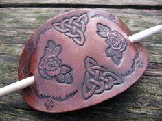 Rose & celta nudo.  Real de cuero mano de pasador de pelo con rosas y celta nudo diseño. Demostrado aquí en caoba con un especial enlucidos antiguo. El borde está ennegrecido para terminar el efecto y la cosa entera es encerada y pulida a un hermoso brillo. Accesorio para el pelo.  Hecho a mano utilizando herramientas tradicionales y los métodos en mi pequeño taller Arreton Craft Village en la hermosa isla de Wight. El pasador se corta de plena flor, piel de espesor completo de la más alta…