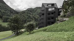 Italian studio Pedevilla Architects has completed a contemporary extension to a traditional Alpine hotel, comprising a monolithic blackened-timber volume.