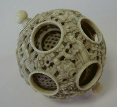 A Chinese ivory seven layer puzzle ball. The outer ball carved depicting mandarin figures among abundant florals. The interior layers with pierced motif.