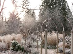 This arbor is the entry point to a large mixed border; it's composed of a trio of simple arches connected by swags of rope. While adding height and scale to the garden, this structure is transparent, allowing the plants beyond to be framed rather than obscured.