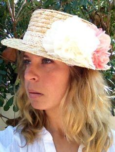 Sombrero canotier decorado con una cinta de ganchillo y dos flores de tela en colores blanco y rosa.