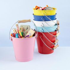 """Colored Buckets: """"[I] took a tip from one of the home improvement stores and got a bunch of clean plastic buckets from the restaurant I work at. We drilled the bottoms and screwed them into a peg board in a rainbow shape."""" — Skye A. via Facebook  Source: Land of Nod"""