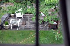crisp white adirondacks on a rectangular tiled patio, low wall around it