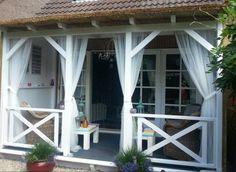 Veranda met rieten dak en klamboe gordijnen tegen de muggen.