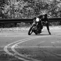 Motorbike rider cornering, in black and white