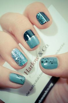 A very artistic nail art design making use of midnight blue and blue gray polish for the base and heart shape details; a silver thin metallic strip is used to separate the colors.