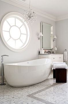 I have never seen a more handsome tub!! The window is amazing and the chandelier lovely! --Jennifer Worts Design-chic, modern spa bathroom design with glossy white soaking tub, beveled mirror, white bathroom vanity, sconces, espresso stools, marble tiles floors, crystal, modern block stools, polished chrome fixtures, chandelier and platinum gray paint wall color.