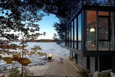 Building Arts Architects has designed a new modern boat house on the shores of Kawagama Lake in Ontario, Canada, that includes dry slip boat storage via marine railway, and a 452 square foot sqm) dwelling space. Ontario Cottages, Boat Storage, Clerestory Windows, Building Art, Wood Siding, Architect Design, Water Crafts, Prefab, Living Spaces