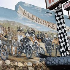 The mural, painted by muralist Robin Golden, stretches about 80 feet across The Wreck's front wall. As the name suggests, the mural celebrates the race that gained notoriety in the movie On Any Sunday 50 years ago. Motorcycle Touring, Motorcycle Racers, Lake Elsinore, 50 Years Ago, Checkered Flag, Veterans Day, Grand Prix, In The Heights, Robin