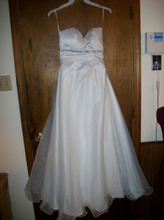 A strapless A-line wedding dress. This is a size 8 with a lined satin skirt with an organza overlay. The hem on this dress is wavy. The cost of this dress is $250.oo US. For contact information go to http://www.sherylsalterationsdesigns.com