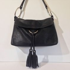 "Alfani Leather Handbag Super soft black leather shoulder bag with silver hardware. Front flap with magnetic closure. Interior has suede and fabric lining, with 2 zip pockets and 1 slip pocket. 2 hanging tassels. Strap drop is 10"" long and has slight wear near the shoulder. Alfani Bags Shoulder Bags"