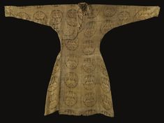 An important Seljuq silk samit robe, Central Asia, 11th century with front opening, flaring skirt, rounded neck and gently tapered sleeves, the samit fabric woven with cream, brown and magenta silk threads, with a design of offset roundels each enclosing paired confronting peacocks flanking a palmette standard reserved on a diamond trellis ground 137cm. max. length