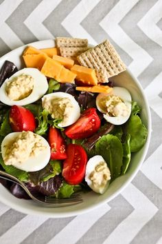 deviled eggs for one, cheeseand crackers, tomatoes,  Served over a salad dressed in olive oil, honey and salt