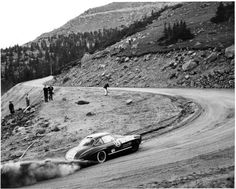 "John Rostek driving his Mercedes Benz 300SL (""Gullwing"") around George's Corner past spectators. Car has sign for Buckley Bros. Denver Pikes Peak 1959"