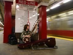 Subway musician playing a sitar, Park St station Red line, Boston