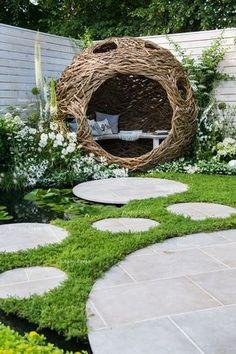 woven willow bird hide (willow sculpture) and concrete circular slabs as a path…