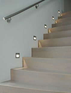 John Cullen stair lights - like the grey wood tread, perhaps combine with glass balustrade and brushed steel handrail ?