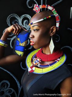 A stunning mix of vibrant colors and this fierce beauty!  Bottom necklaces from the Maasai tribe of Kenya and the red one from Samburu tribe also of Kenya.  Ndebele neckpiece from South Africa as a head band and Maasai necklace as a crown.  Wooden earrings with beautiful colored thread embellishments and jute clutch with Ankara fabric also hand made by artisans in Kenya.   Jewelry and accessories available on my online store  InfiniteMiss.Etsy.com.