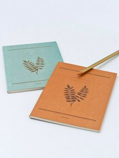 Kraft paper notebooks with leaf designs.