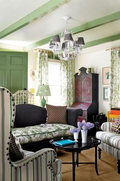 In a nod to English country style, the green living room in this renovated Catskills schoolhouse is filled with antiques, sculptural furniture pieces, and botanical patterns and prints on the walls. For a twist on the classic look, decidedly off-beat pieces, including silver scallop sconces, giraffe-print pillows, and a tropical-inspired chandelier were added.
