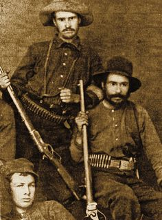 Ready for the hunt, the frontiersman at right packs an 1873 Winchester, while his companion (far right) holds a heavy, octagon-barreled 1874 Sharps. The unarmed man may be their skinner. The differences in ammo size in each hunter's belt reveal who was going after the big game—the Sharps shooter. – Courtesy Herb Peck Jr. Collection –