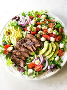 This Caprese Steak Salad screams summer! Balsamic marinated Flat Iron Steak, tomatoes, mozzarella, avocado, and basil in this refreshing, delicious salad. the-girl-who-ate-everything.com