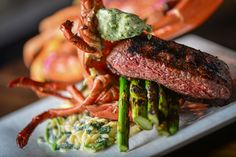 Grilled Surf n' Turf: Char grilled sirloin steak, grilled lobster, asparagus, orzo pasta, and herbed butter.